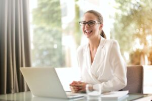 corporate woman smiling in front of a laptop showing health and wellness