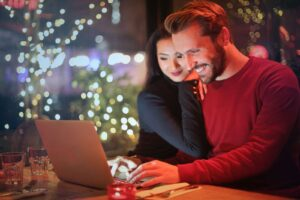 a man and a woman smiling in front of a laptop online